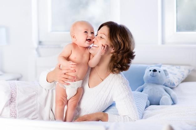 Moeder en baby op een wit bed