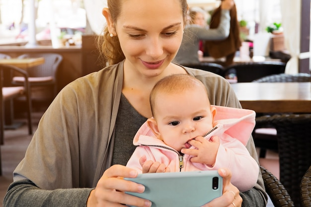 Moeder en baby outddors in een restaurant kijken naar kartons, selfie maken