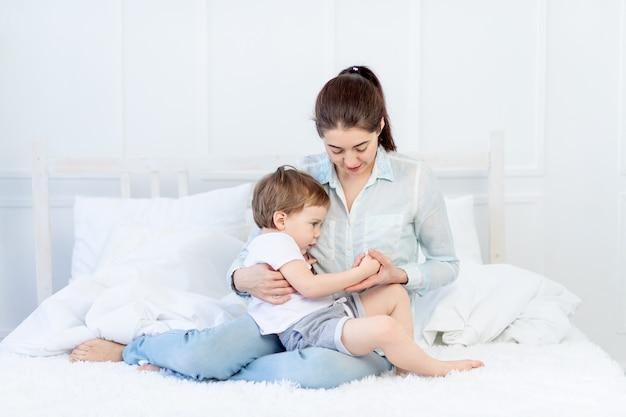 Moeder en baby praten thuis op het bed het concept van de relatie tussen ouders en kinderen