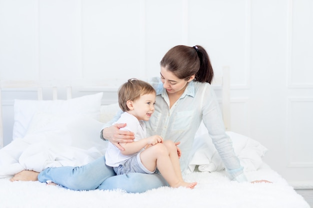 Moeder en baby praten thuis op het bed, het concept van de relatie tussen ouders en kinderen.