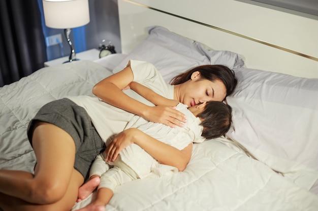 Moeder en baby slapen op bed thuis