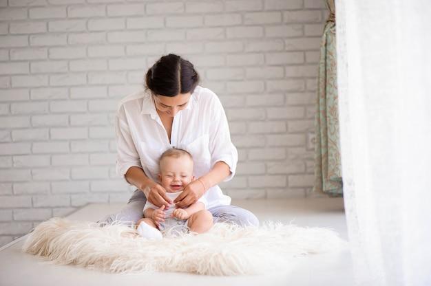 Moeder en baby spelen in de slaapkamer
