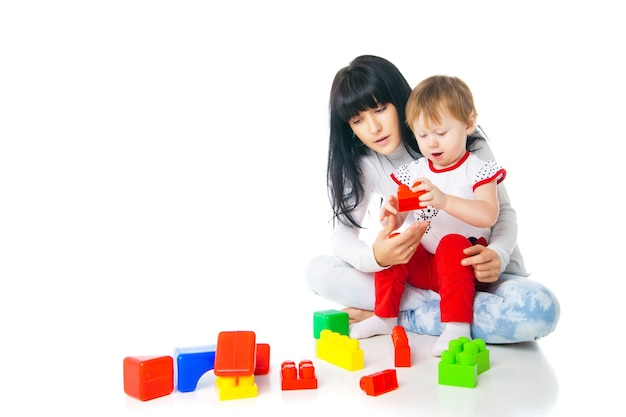Moeder en baby spelen met bouwstenen speelgoed geïsoleerd op wit