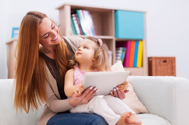 Moeder en baby spelen thuis op de tablet