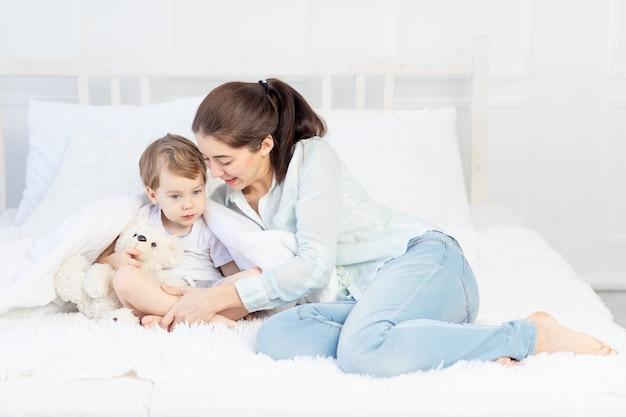Moeder en baby spelen thuis op het bed het concept van familie- en ouder-kindrelaties