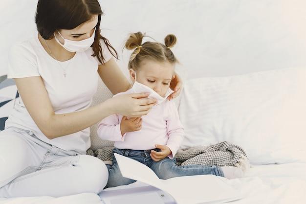 Moeder en baby thuis met medische maskers