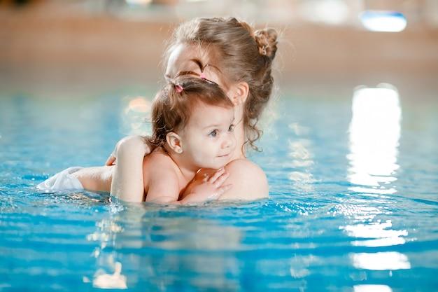 Moeder en baby zwemmen in het zwembad.
