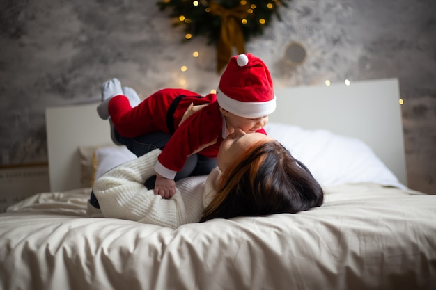 Moeder en babyjongen in het kerstmis verfraaide huis