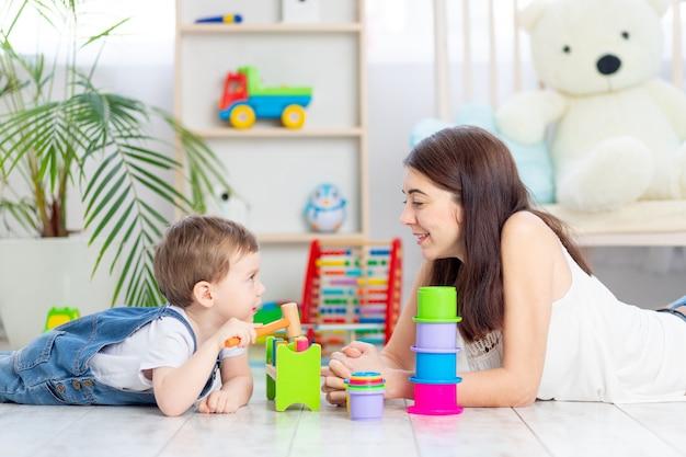 Moeder en babyjongen spelen thuis met educatief speelgoed in de kinderkamer. een gelukkig, liefdevol gezin.