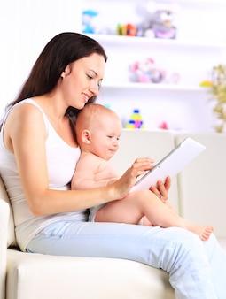 Moeder en babykind zijn op zoek om thuis tabletcomputer op de bank te spelen en te lezen