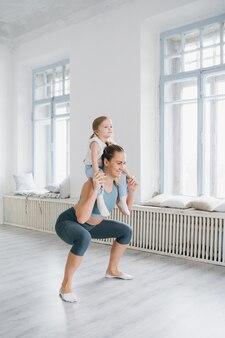 Moeder en babymeisje doen oefeningen samen in de sportschool