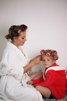 Moeder en babymeisje zijn in badjassen en krulspelden op haar hoofd.