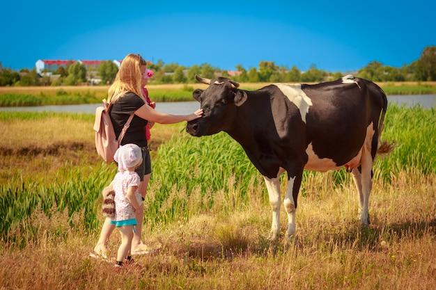 Moeder en de kinderen aaien de koe