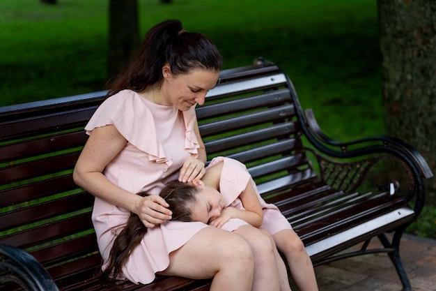 Moeder en dochter 5-6 jaar wandelen in het park in de zomer, de dochter ligt op de schoot van haar moeder op een bankje, het concept van een gelukkig gezin, de relatie van moeder en kind, moederdag