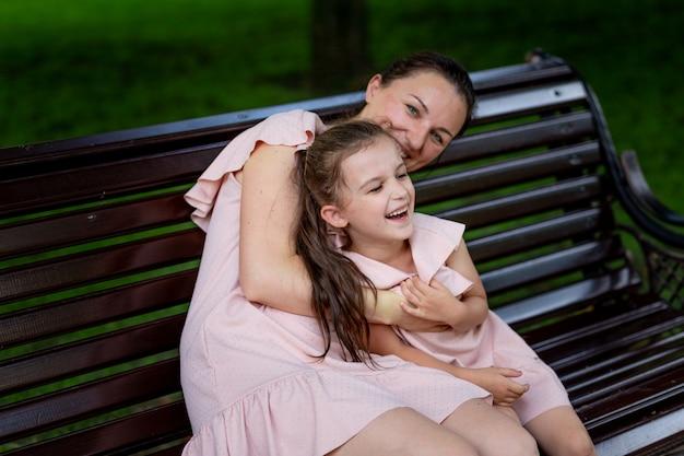 Moeder en dochter 5-6 jaar wandelen in het park in de zomer, dochter en moeder lachen op een bankje, het concept van een gelukkig gezin, de relatie van moeder en kind, moederdag