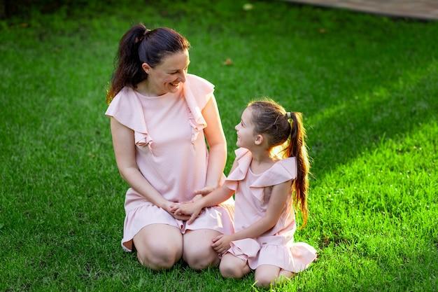 Moeder en dochter 5-6 jaar wandelen in het park in de zomer, moeder in gesprek met haar dochter zittend op het gras, het concept van een gelukkig gezin, moeder-kind relaties, moederdag