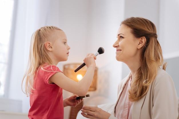 Moeder en dochter. aangenaam aardig vrolijk meisje dat een borstel vasthoudt en naar haar moeder kijkt terwijl zij make-up doet