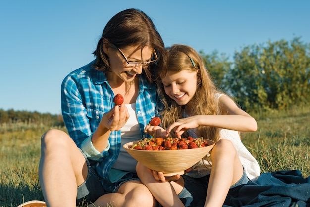 Moeder en dochter aardbeien eten