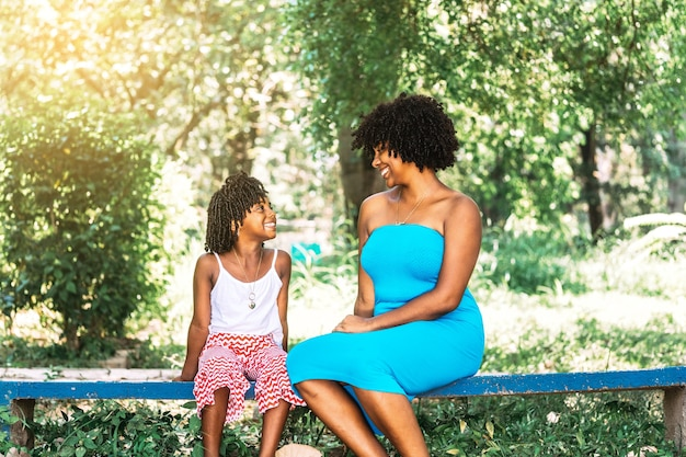 Moeder en dochter afro-amerikaanse etniciteit zitten in een park naar elkaar te kijken en te praten