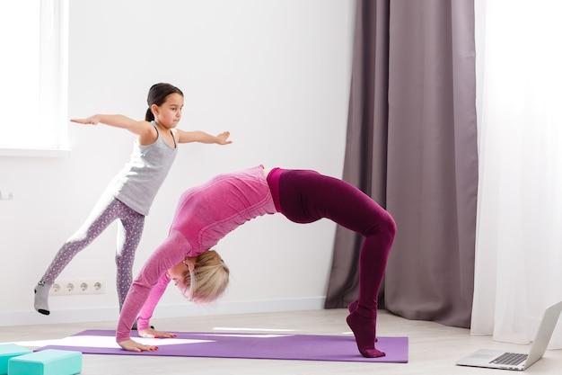Moeder en dochter beoefenen thuis yoga