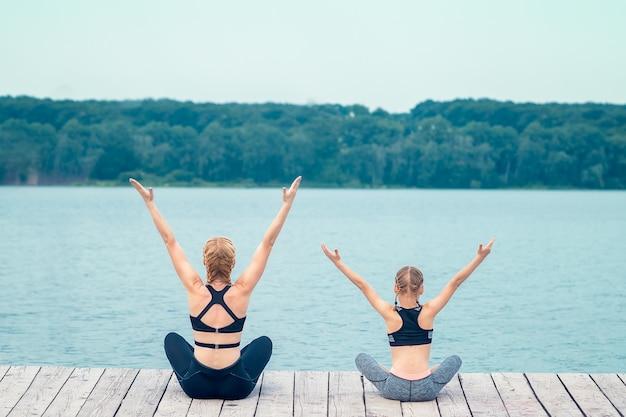 Moeder en dochter beoefenen van yoga op een pier