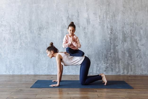 Moeder en dochter beoefenen yoga in de sportschool en mediteren samen