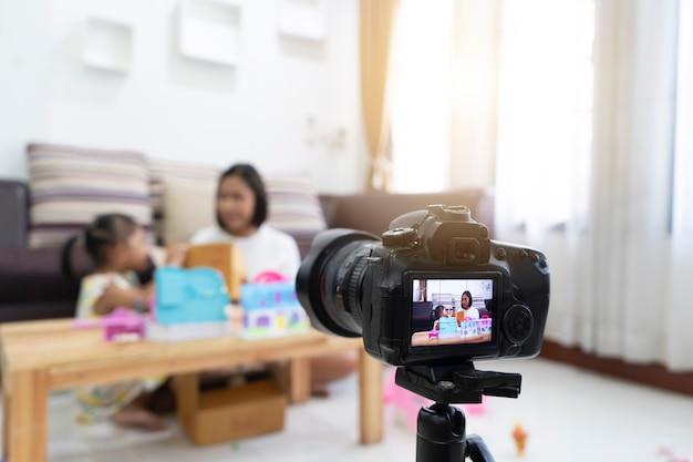 Moeder en dochter beoordelen speelgoed thuis. met opname maken video blogger camera