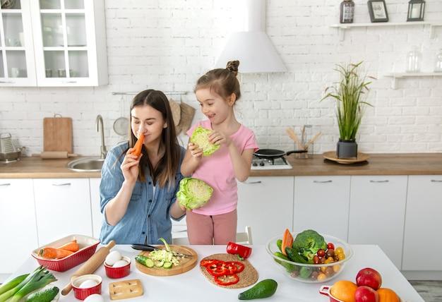 Moeder en dochter bereiden een salade in de keuken. veel plezier en speel met groenten