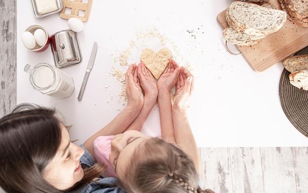 Moeder en dochter bereiden hartvormige koekjes voor op een grote witte keukentafel.