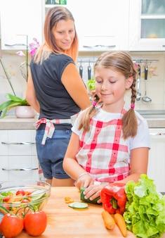 Moeder en dochter bereiden in keuken groenten voor