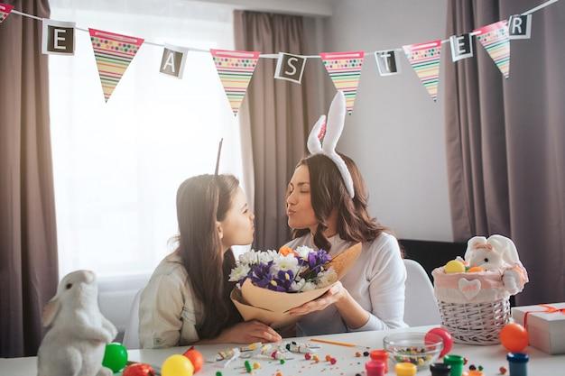 Moeder en dochter bereiden zich samen voor op pasen in de kamer. ze houden één boeket bloemen vast. mensen zitten in de kamer met decoratiesnoepjes op tafel. feestelijk.