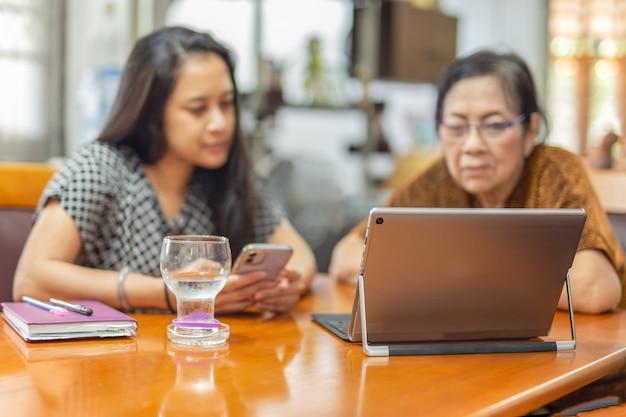 Moeder en dochter besteden tijd samen aan het kijken naar film op laptop als familietijd.