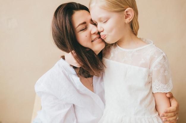 Moeder en dochter binnenlevensstijlportret. moeder knuffels met haar kleine grappige dochter.
