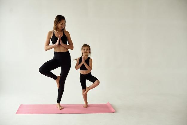 Moeder en dochter brengen de ochtendyoga-oefening door.