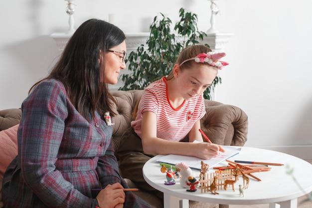 Moeder en dochter brengen samen tijd door, zitten op de bank, praten en tekenen met kleurpotloden. vrije tijd moeders en dochters. meisje tekent op papier