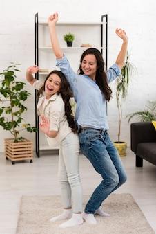Moeder en dochter dansen in de woonkamer