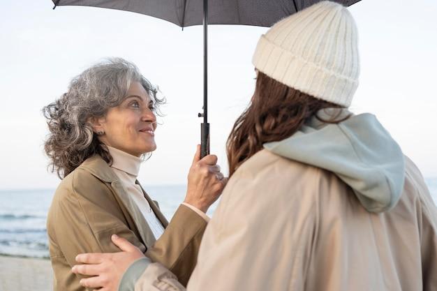 Moeder en dochter delen een teder moment op het strand onder een parasol