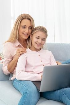 Moeder en dochter die aan laptop werkt