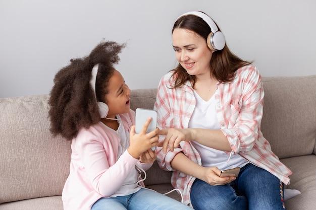 Moeder en dochter die aan muziek thuis luisteren
