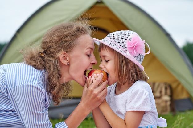 Moeder en dochter die appel eten dichtbij een tent in weide of park. gelukkige familie op picknick op de camping