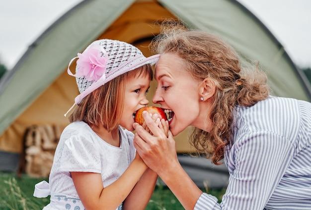 Moeder en dochter die appel eten dichtbij een tent in weide of park. gelukkige familie op picknick op de camping.