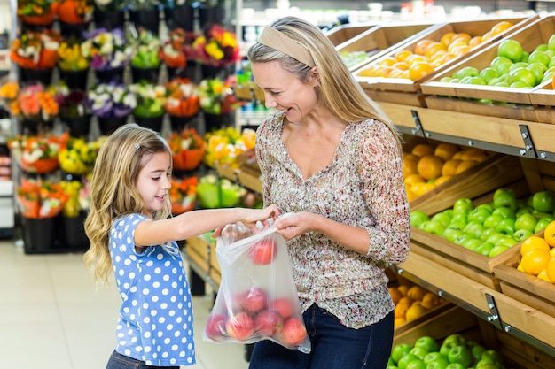 Moeder en dochter die appel in supermarkt uitkiezen