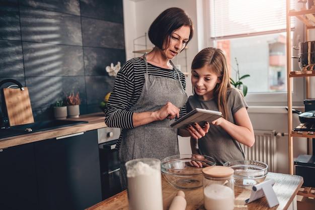 Moeder en dochter die appeltaartrecept zoeken op de tablet