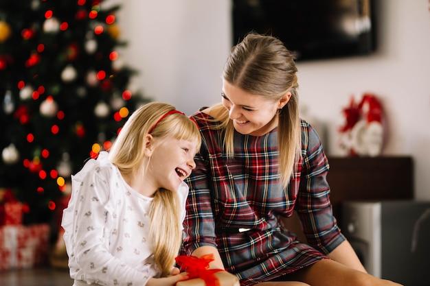 Moeder en dochter die bij kerstmis lachen