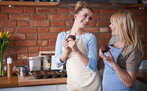Moeder en dochter die chocolademuffins eten
