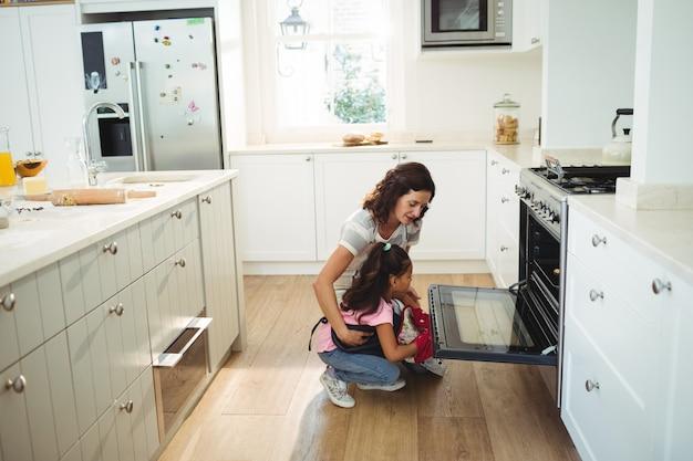Moeder en dochter die de gebakken koekjes in oven controleren