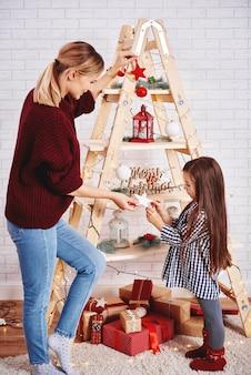Moeder en dochter die de kerstboom versieren