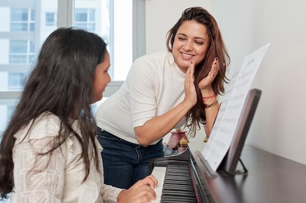 Moeder en dochter die de piano spelen
