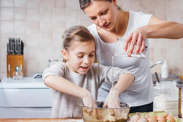 Moeder en dochter die deeg maken