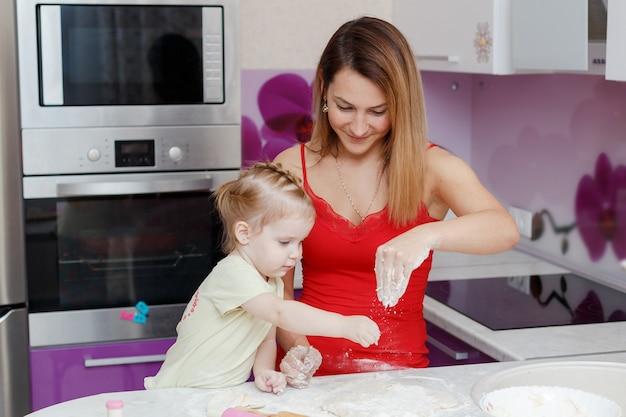 Moeder en dochter die deeg thuis keuken maken